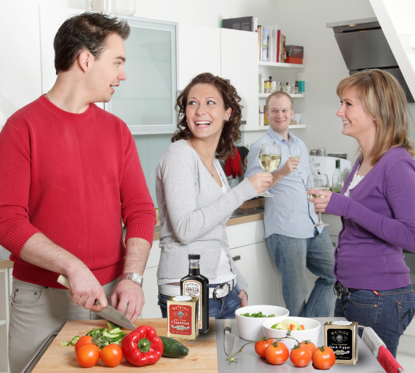 Two couples in kitchen, cooking with Watkins products